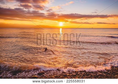 Surfer In Ocean At Bright Warm Sunset Or Sunrise. Surfing In Ocean