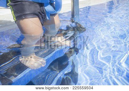 Little Boy Steps Down The Swimming Pool Ladder With Foot Underwater. He Wears A Float Belt