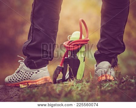 Closeup Of Sportsman Legs In Sneakers With Bottle And Expander. Image With Vintage Toning
