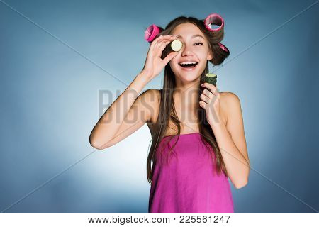 Happy Woman With Big Curlers On Her Head Holds A Cucumber In Her Hand