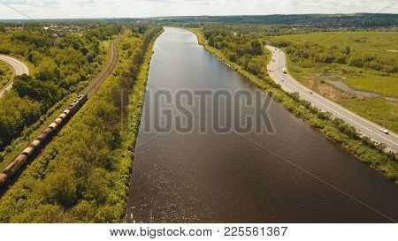 Freight Train With Cisterns And Containers On The Railway. Railway And Highway With Cars. Aerial Vie