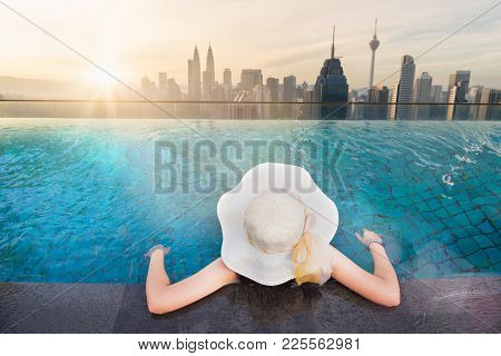 Summer Travel Concept, Vacation Relaxing Concept, Women Enjoy And Relaxing In Swimming Pool On Roof