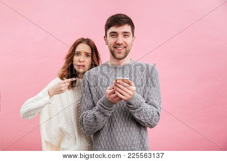 Portrait of young loving couple dressed in sweaters standing with mobile phone isolated over pink background, smiling man and angry woman