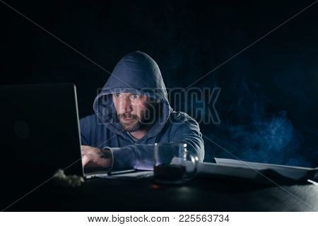 Male Hacker Sitting At Table Looking At Laptop And Typing Something
