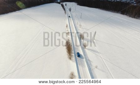Car On Winter Road In The Countryside Middle Of The Field. Winter Forest, Field. Aerial View: Winter
