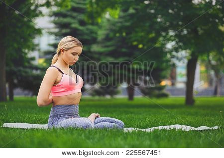 Woman Outdoors Making Asana Exercises. Girl Do Reverse Prayer Pose, Back And Shoulders Stretching. W