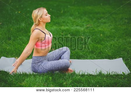 Fitness, Woman Training Yoga In Bound Angle Pose Outdoors In The Park, Copy Space. Young Slim Girl M