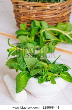 Mint Twigs In The Pounder On White Wooden Table