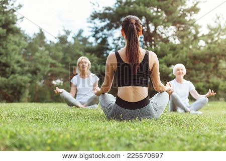Yoga Coach. Nice Attractive Young Woman Sitting Opposing Her Group And Meditating While Having A Yog