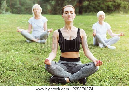 Calmness In Soul. Delighted Nice Calm Women Sitting On The Grass And Meditating While Looking For Ha