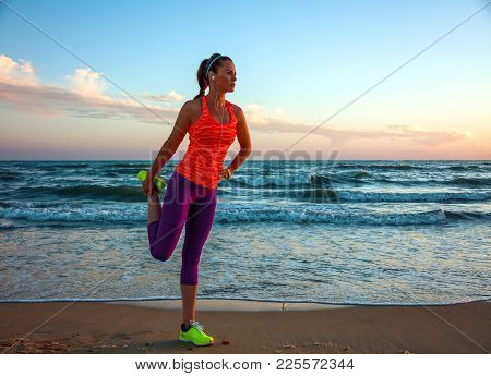 Fit Woman In Sports Gear On Beach At Sunset Stretching
