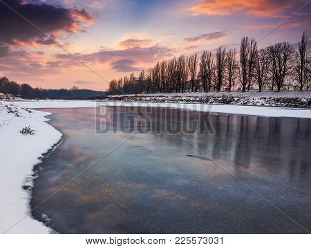 Beautiful Sunset On The Frozen River. Location Nealezhnosti Embankment In Uzhgorod. Beginning Of The