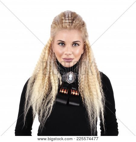 Young Girl With Long Blond Hair In A Black Sweater With A Brooch On A White Background.
