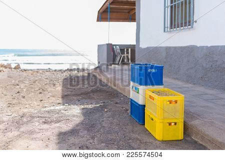 Beverage Crates With Empty Soft Drink Bottles Stacked On Ground Besides Restaurant Terrasse On Beach