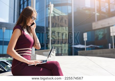 Smiling Businesswoman Talking On Phone And Working On Laptop, Sitting On Bench Outdoors Near Modern