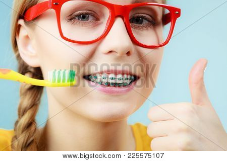 Dentist And Orthodontist Concept. Young Woman With Blue Braces Cleaning And Brushing Teeth Using Man
