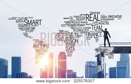 Businessman In Suit Writing Business-related Terms In Form Of World Map While Standing On Broken Bri