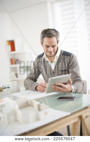 An Architect Working On The Office With A Tablet