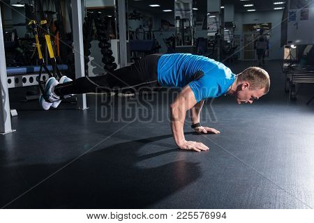 Man In The Gym Does Push-ups With His Legs On The Suspension. Training Athlete