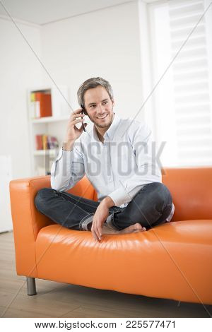An Attractive Man Smiling And Phone On A Couch