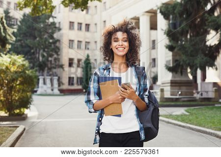 Happy Smiling African-american Student Girl With Backpack At University Background. Woman With Mobil