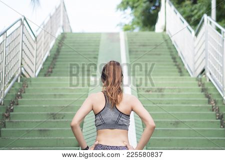 Asian Young Woman Warm Up Body Stretching Before Morning Exercise And Jogging Under Warm Light Morni