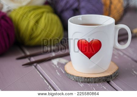 White Cup Of Tea With A Red Printed Heart On The Background Of Colorful Yarn And Knitting Needles. W