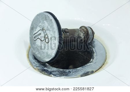 Concept on the repair or poor quality of sanitary ware. Damaged sewer hole with corrosion elements  on which lies a broken metal button or cork with the image of the foot of a bathtub or shower. Close-up. poster