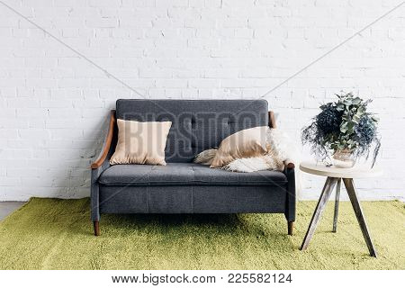 Comfy Couch In Modern Living Room With White Brick Wall And Flower Pot On Table, Mockup Concept