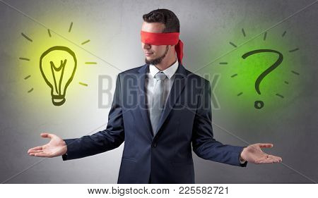 Covered eye businessman with bulb and question sign symbols around