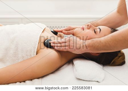 Beautiful Woman Getting Hot Stones Shoulders Massage In Spa Salon. Beauty Treatment Therapy, Wellnes