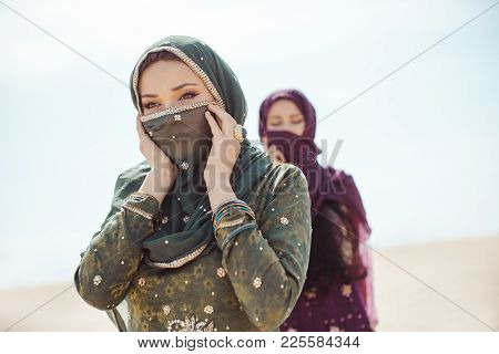 Desert women thirsty dehydrated tired walking outdoors. Dehydration, overheating, thirst and heat stroke concept image with two sisters in desert nature. Beautiful mixed race asian caucasianl arabian girls lost in desert during journey. poster