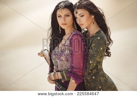 Travel Concept. Adventure Of Two Sisters Serious Princesses Standing In The Desert And Looking At La