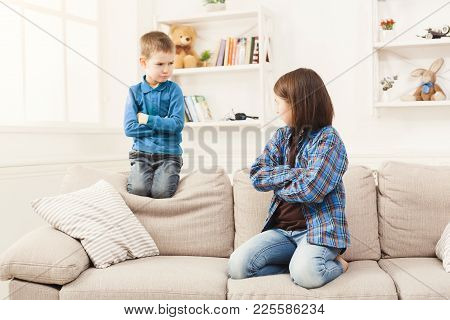 Little Quarrel. Small Pretty Girl And Her Brother Offended, Sitting On Couch At Home With Hands Cros