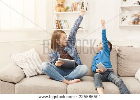 Two Kids With Gadgets. Siblings With Raised Hands Won Online Game On Tablet. Happy Children Celebrat