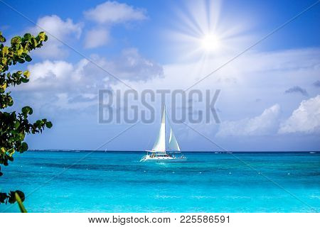 A Small White Sailboat With People Aboard Crusing Out On An Aqua Ocean Under A Cloudy Sky In The Aft