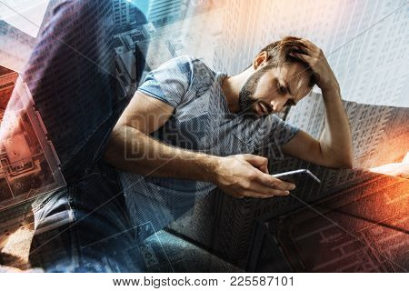 Realizing Mistakes. Young Unhappy Emotional Man Sitting On The Floor With His Hand Touching His Head