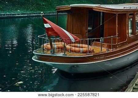 A Boat With National Flag Of Latvia Sailing In The Park Near Latvian National Opera In Riga Latvia.
