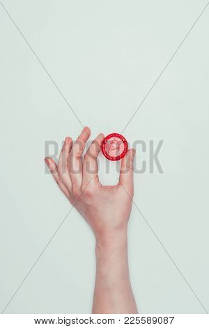 Partial View Of Woman Holding Opened Condom In Hand Isolated On Grey