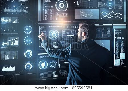 One touch. Calm clever elegant programmer feeling interested while standing in his modern convenient office and touching the transparent screen of a big futuristic device poster