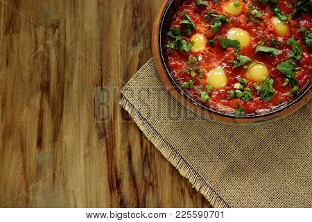 Fried eggs with tomato sauce and parsley in a cast iron pan. Shakshuka a traditional meal of the Jew