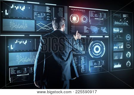 Smart employee. Experienced clever young programmer dealing with the problem of cyber security while standing in front of a giant transparent screen of a futuristic device poster