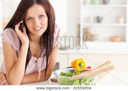 Joyful woman using a cellphone in a kitchen