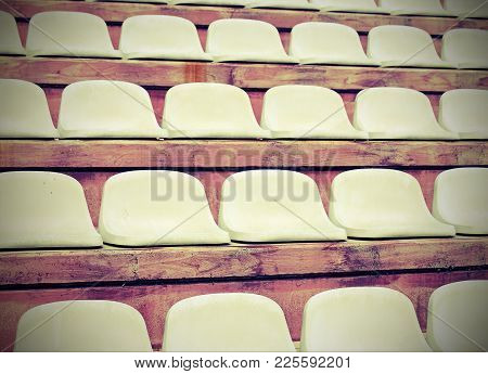White Seats On Stadium Bleachers Without  People Before The Meeting Sports With Vintage Effect