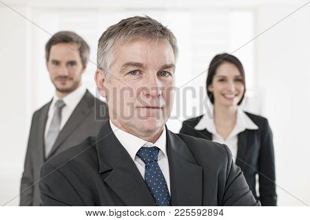 A Senior Businessman At Foreground And His Team Behind Him