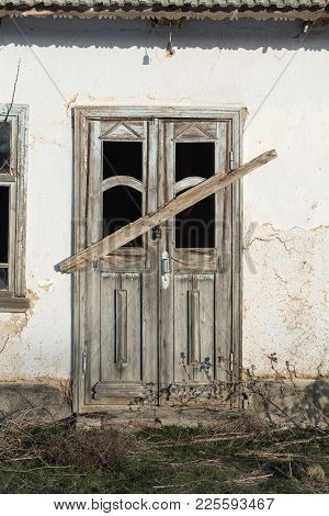 The Old Wooden Boarded-up Door Of The Clay House
