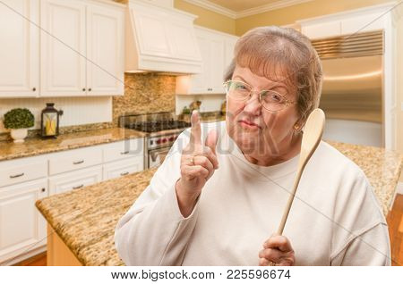 Senior Adult Woman Scolding with The Wooden Spoon Inside Kitchen.