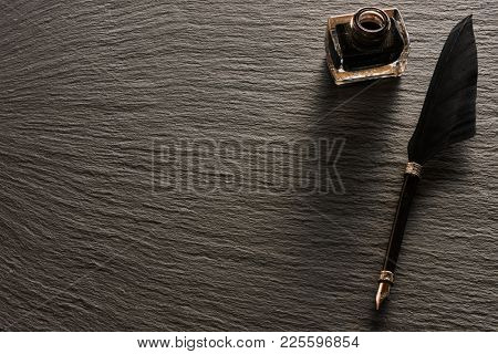 Feather pen and inkwell over slate background