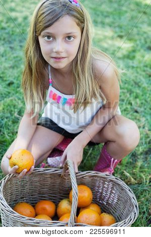 Smiling Little Girl Playing Outdoors With Oranges