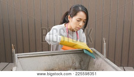 Woman cleaning barbecue oven with Scour Pad